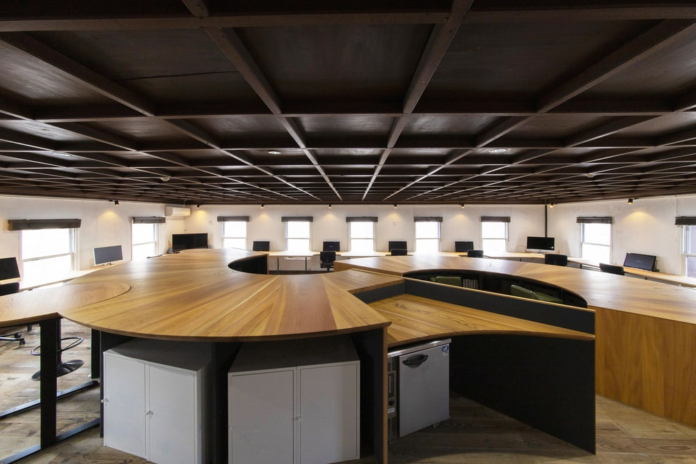 This is another view of the unique curved wooden structure that can house multiple people with separate work surfaces.
