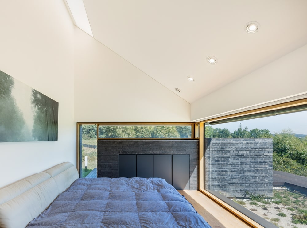 The bedroom has glass walls on two sides to brighten the platform bed that is topped with a bright beige shed ceiling.