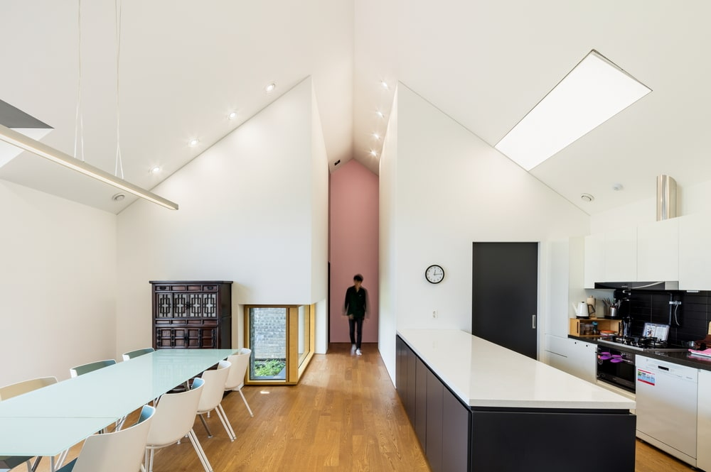 This is a full view of the kitchen and dining area with white walls and white cathedral ceiling with a large kitchen island and a long dining table across from it.