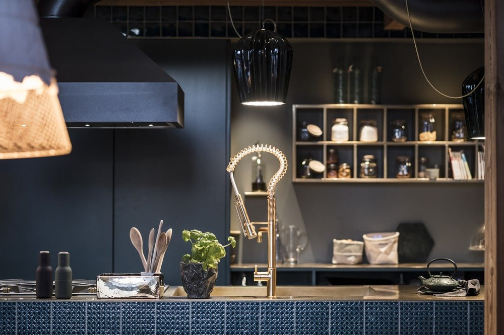 This is a close look at the dark kitchen with shelves on the far wall lit with warm lighting.