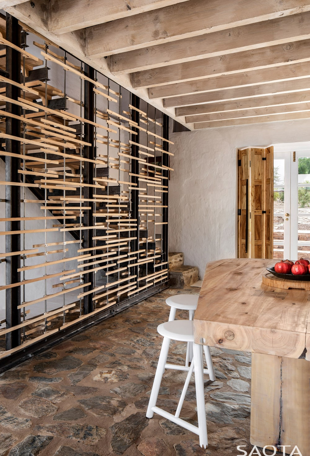 A few steps from the eat-in kitchen is the staircase that is adorned with wooden accents and a beamed ceiling.