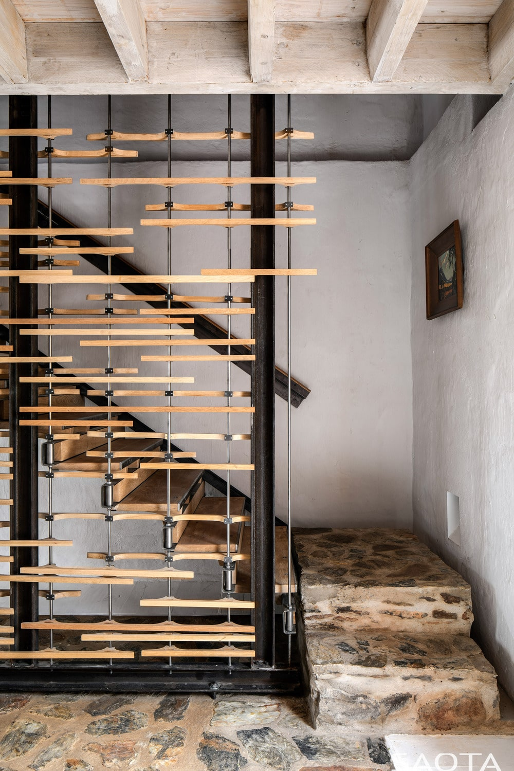 This is a close look at the stair case with steps that match the mosaic rustic stone floor adorned with wooden accents on the side.