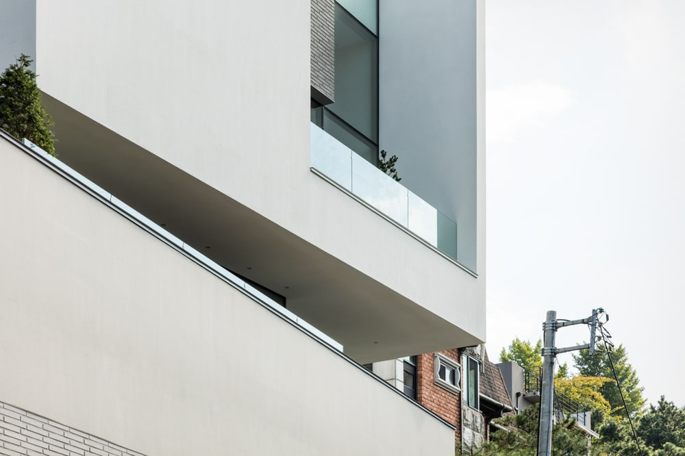 This is a closer look at the upper floor balconies and glass windows supported by concrete structures.