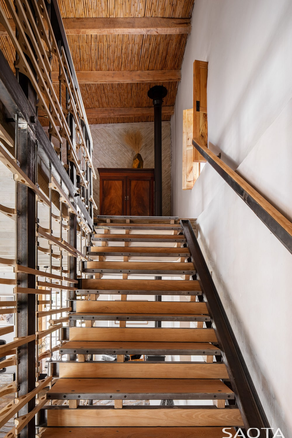 This is a look up the staircase with wooden steps, a wooden window on the side and wooden dresser at the landing above.