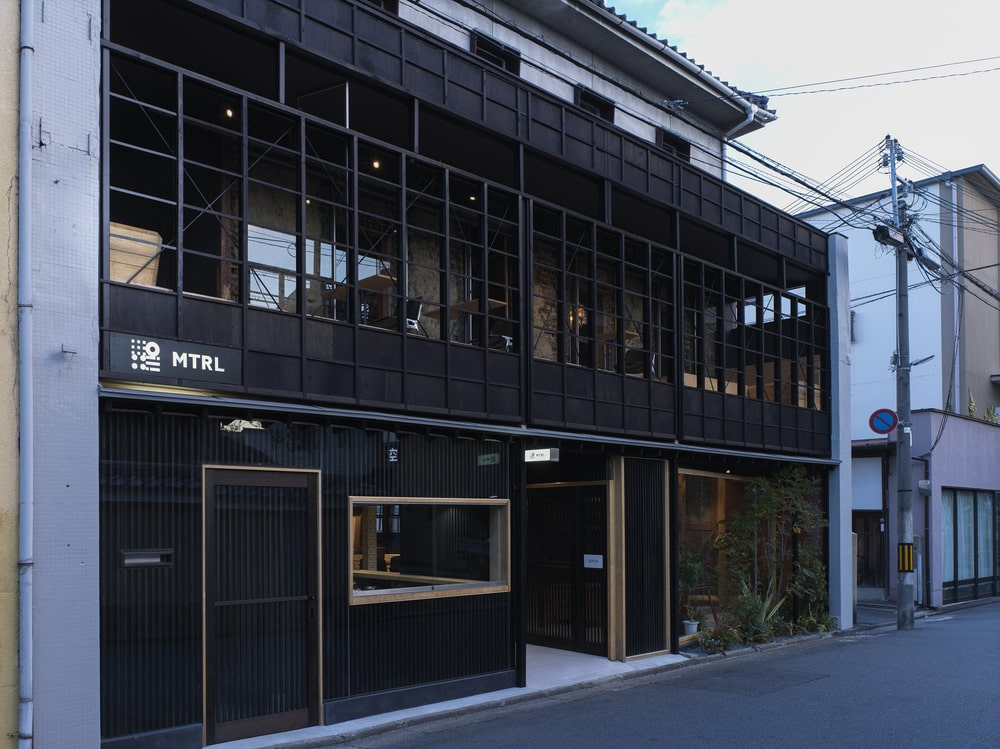 This is a front view of the building exterior showcasing a black tone to its exterior walls and windows.