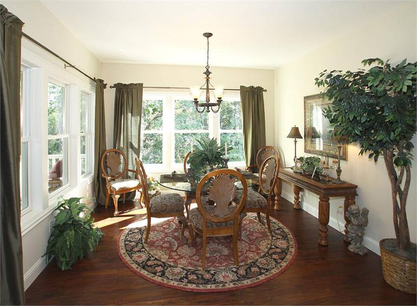 This is the dining room that has a glass-top round dining table surrounded by wooden chairs and brightened by the large set of windows on the far wall.