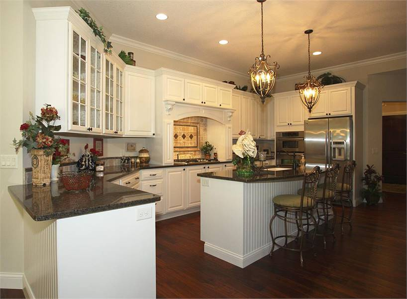 This large kitchen has a large kitchen island topped with a couple of decorative pendant lights. This has white cabinetry that matches those of the peninsula contrasted by the hardwood flooring.