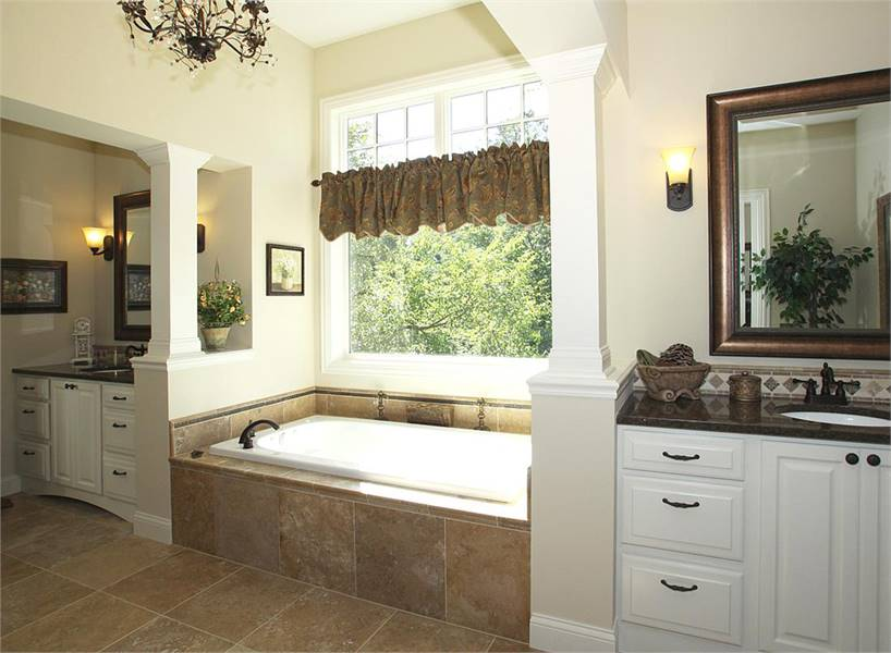 This is a close look at the bathroom with a large bathtub in the middle of two white vanities and in an alcove with a large window above.