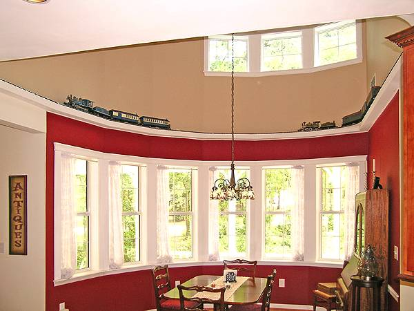 This is a full view of the dining area with curved red walls brightened by the row of curved windows and tall ceiling that has transom windows.