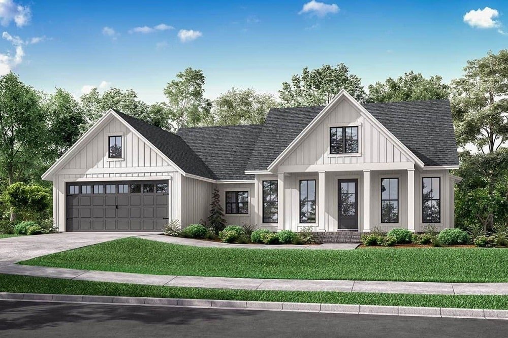 The dark gray roof of this Farmhouse-style home matches well with the large gray garage door on the left side of the house. These are then complemented by the simple landscaping and concrete driveway.