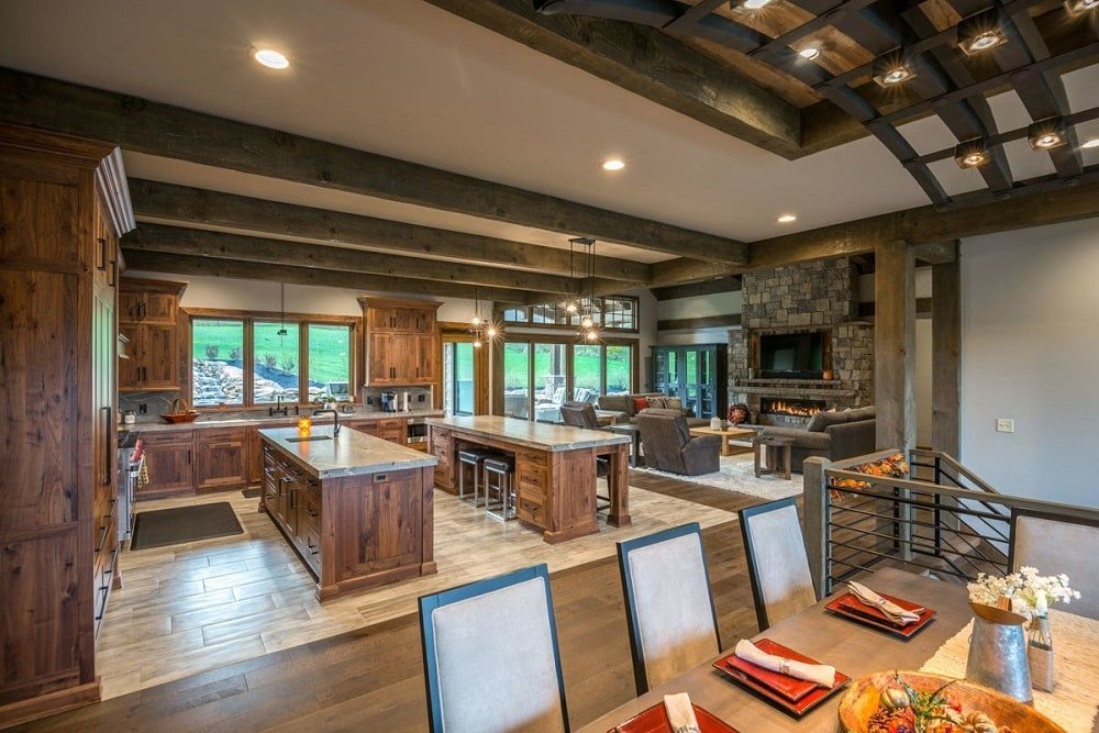 This is a full view of the kitchen from the vantage of the dining area. The kitchen has two kitchen islands and one L-shaped peninsula with matching dark wooden cabinetry that ,atches well with the exposed beams of the ceiling above.
