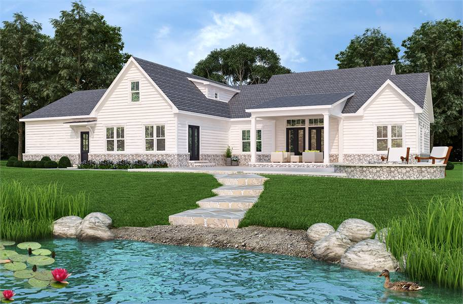 This is a view of the back of the house that has grass lawns and stone steps that lead to the small pond with decorative stones on the side.