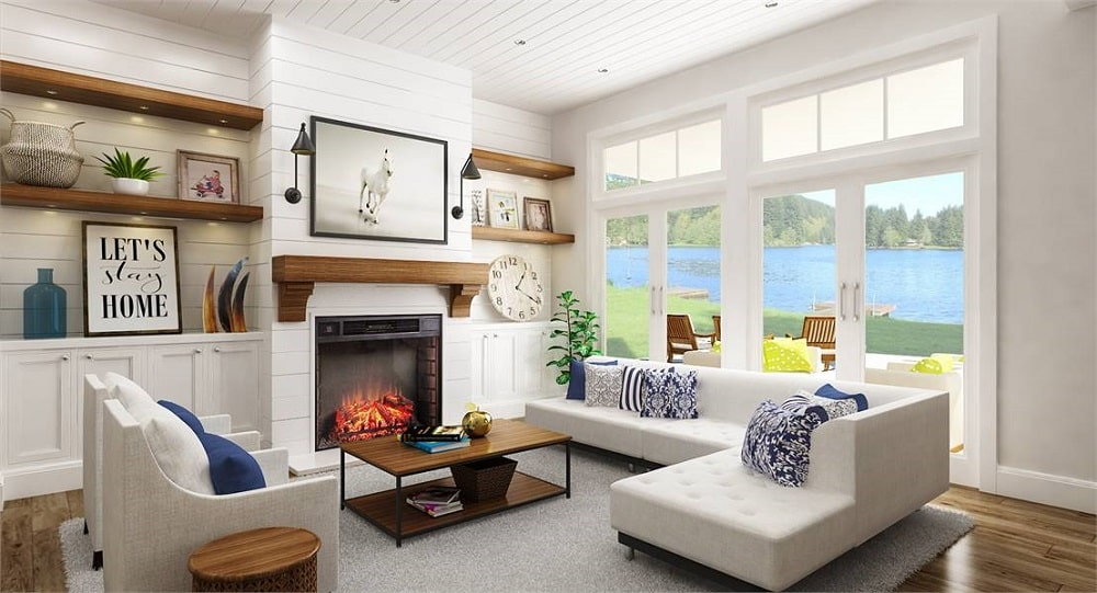 The light tone of the L-shaped sectional sofa across from the fireplace matches well with the white shiplap walls and ceiling that are illuminated by the large windows.