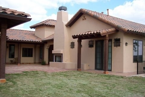 This is a close look at the house exterior with adobe exterior walls that pair well with the outdoor fireplace, clay tile roof and terracotta walkways.