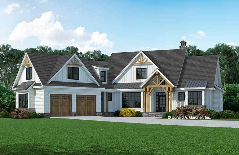 This is a front view of the farmhouse-style home with large dormer windows and wooden tone to its garage doors and pillars of the main entrance as accent.