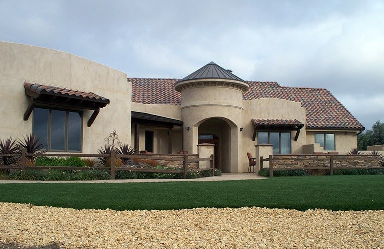 This is a southwestern-style home with adobe exterior walls that has an earthy tone complemented by the terracotta roof tiles and surrounding landscape.