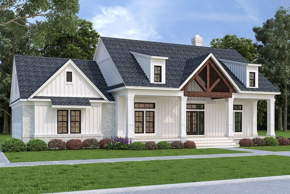 This is a two-story modern farmhouse-style home with dormer windows and multiple windows in a row with the door. These are complemented by the wooden beams above the main entrance and the landscaping that has shrubs.