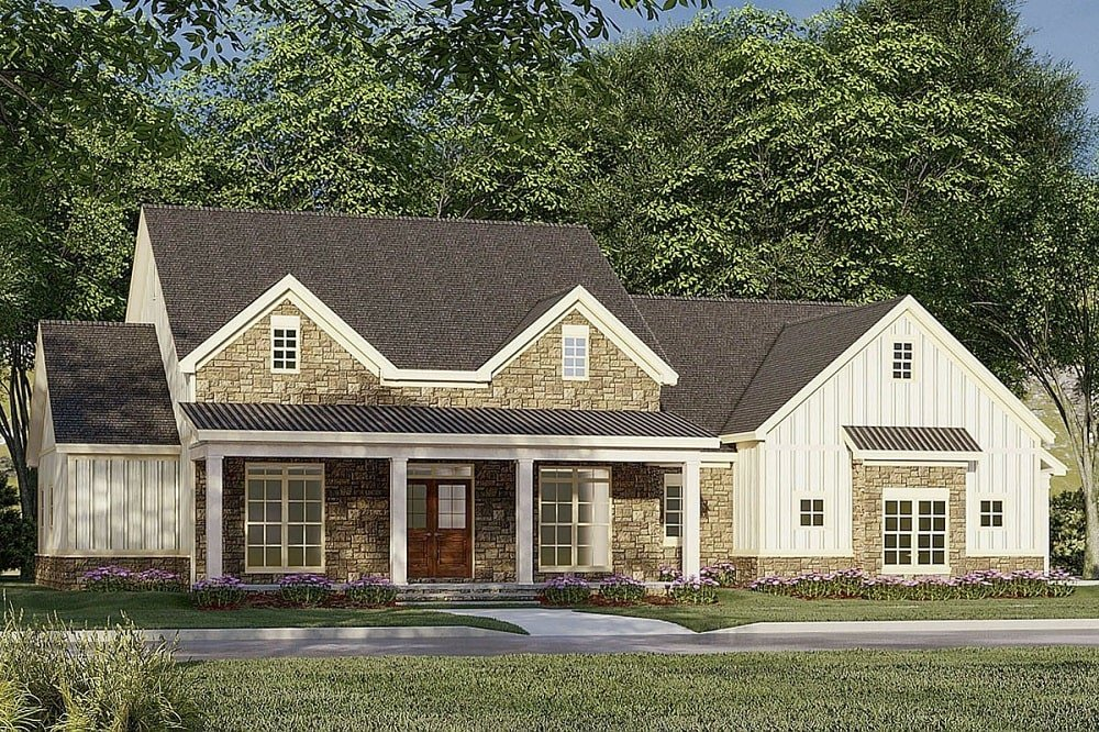 This is a front view of the exterior of this modern farmhouse-style home with stone siding accent on the main structure to complement the dark gray roof and bright beige exterior walls.