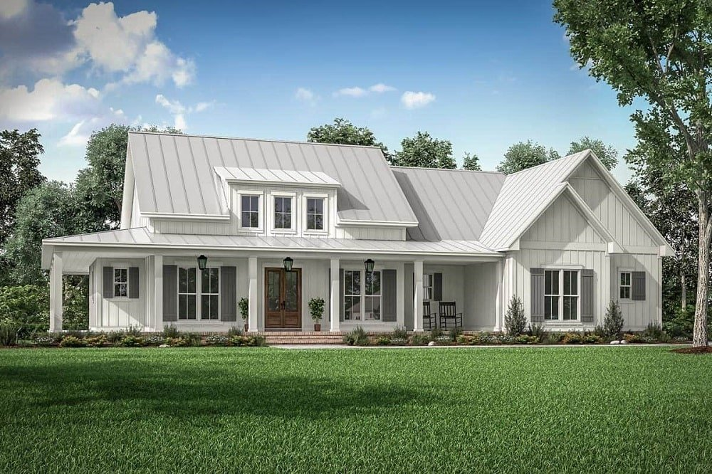 This is a three-bedroom farmhouse-style home with a unique row of dormer windows above the covered main entrance with a brown door that stands out against the bright beige exterior walls and ceiling.