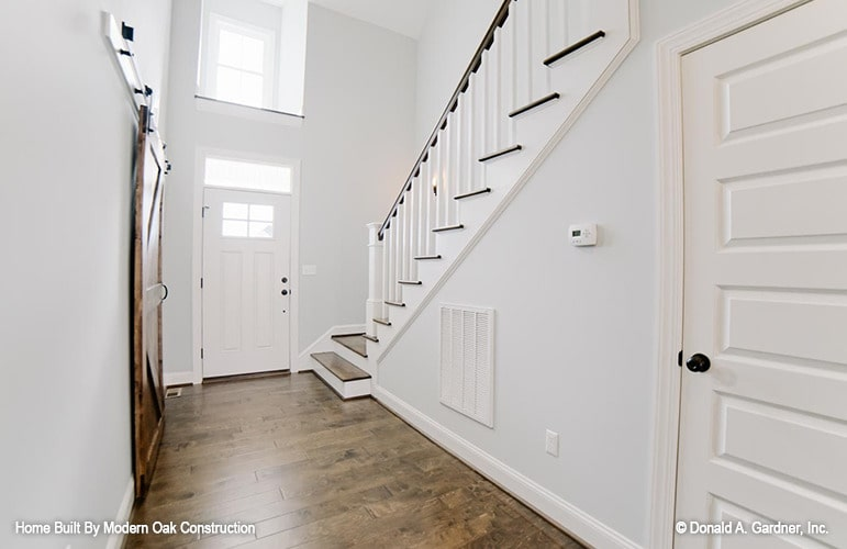 Foyer with a white entry door, a clerestory window, and a staircase leading to the family bedrooms.