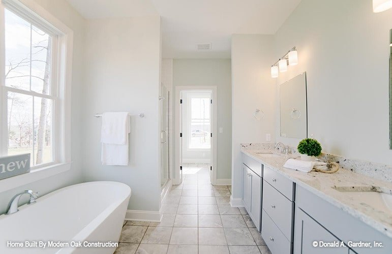 The primary bathroom is equipped with a walk-in shower, a freestanding tub, and a double sink vanity.