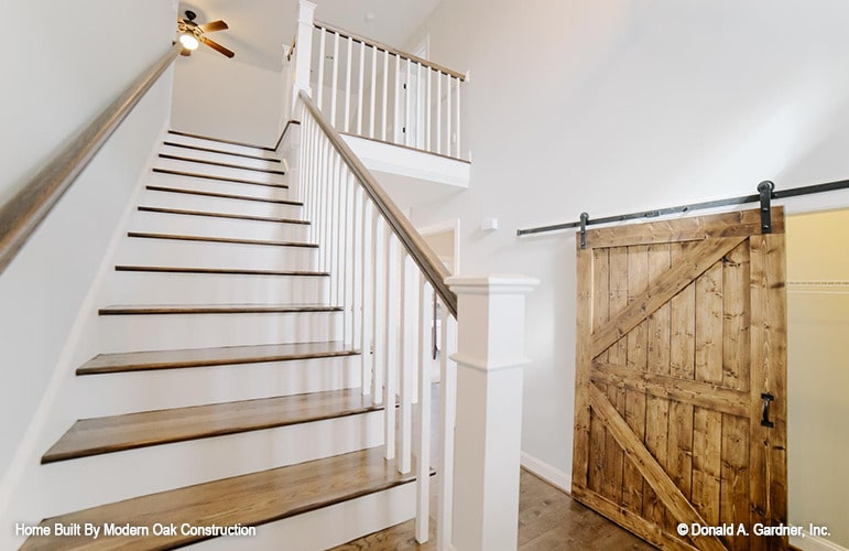 Across the staircase is a large barn door that conceals the storage space.