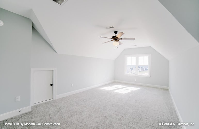 Bright bonus room with carpet flooring, light gray walls, and a vaulted ceiling mounted with a fan.