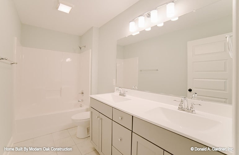 This bathroom offers double sinks, a toilet, and a shower and tub combo.