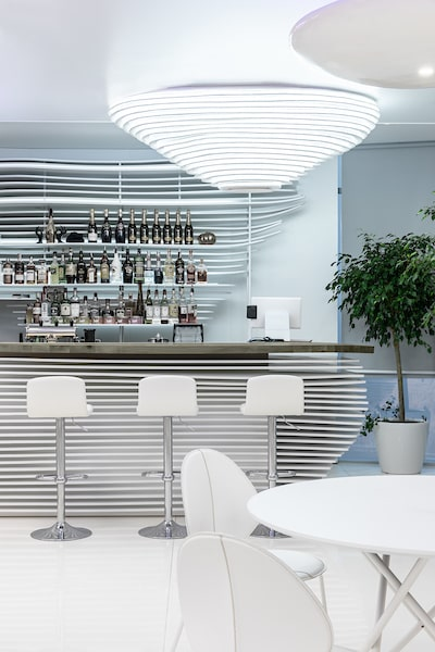 This is a closer look at the bar with similar striped designs on its panels, shelves and lighting.