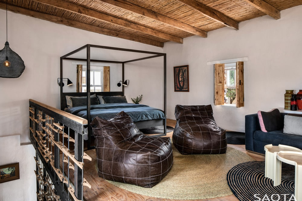 The landing, you can see the four-poster bed paired with bean bag chairs and topped with a wooden beamed ceiling.