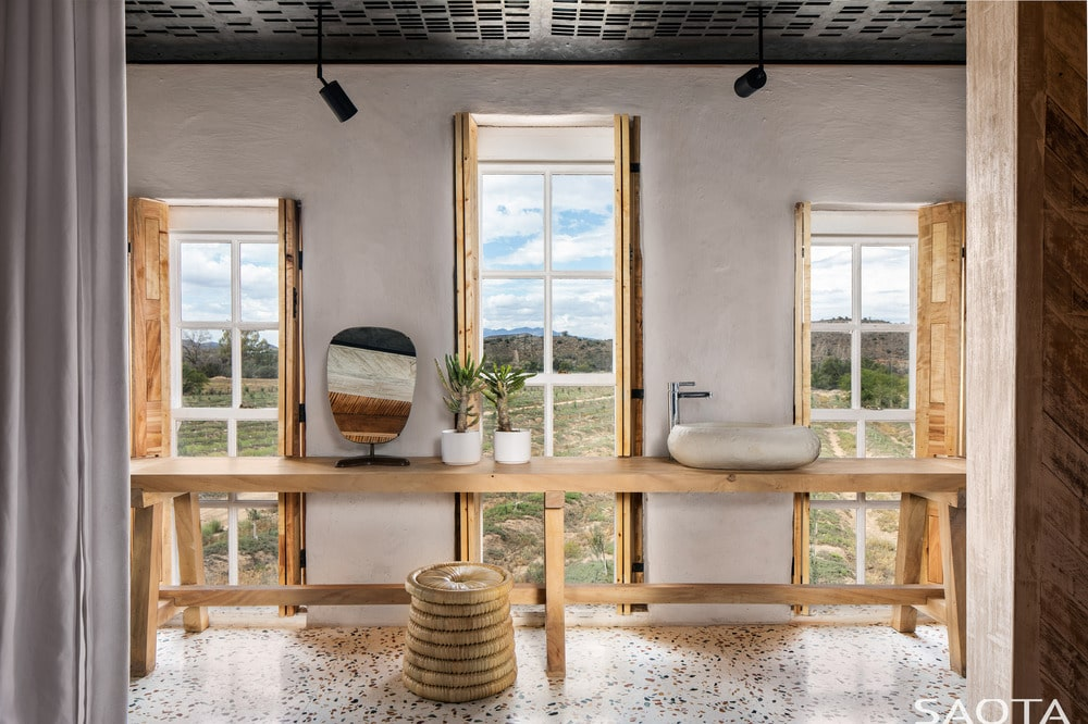 The spacious bathroom has a rustic feel to its long wooden table that serves as the support for the sink paired with tall windows.
