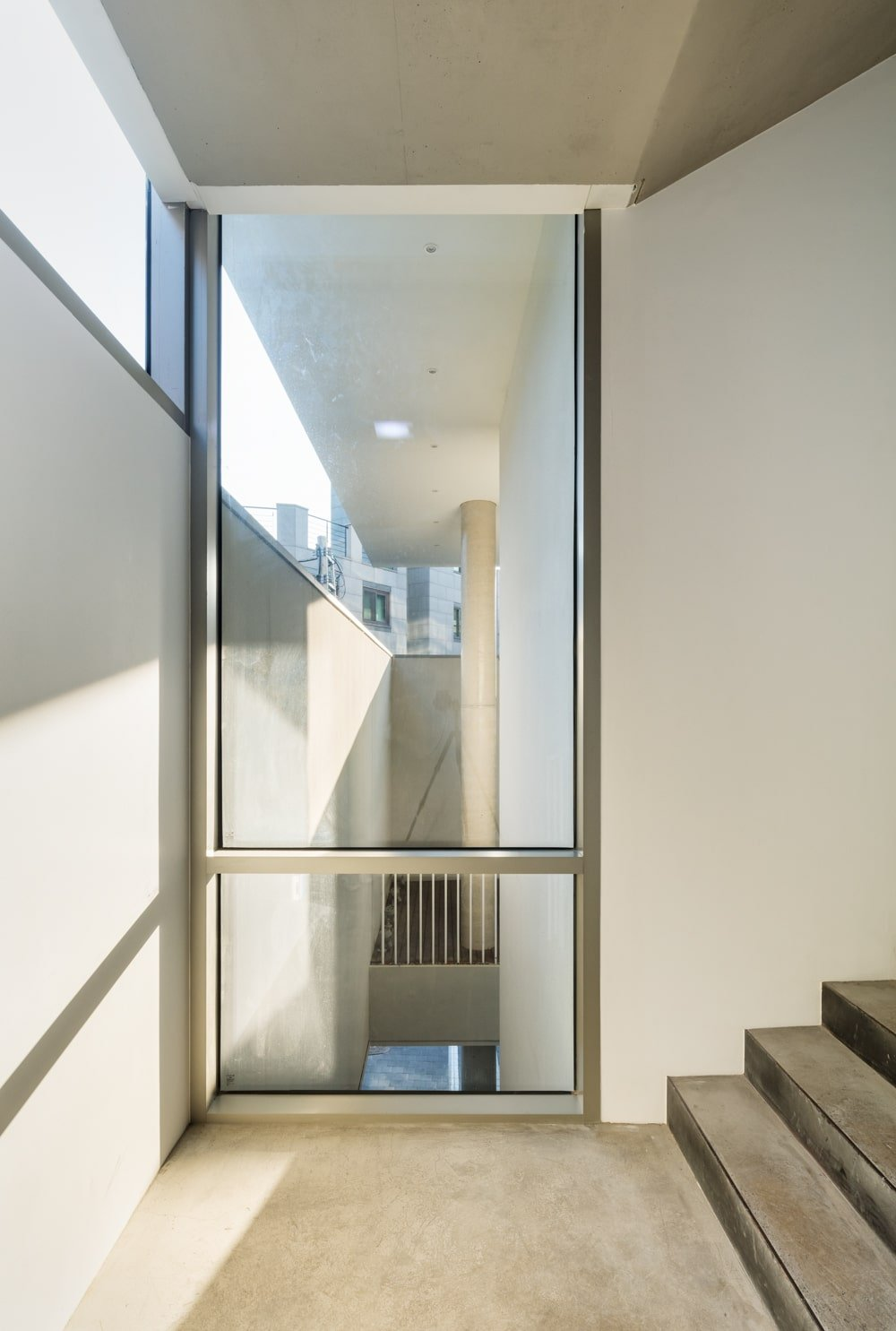 This is a close look at the staircase with beige walls and a large glass window on the corner by the landing for natural lights.