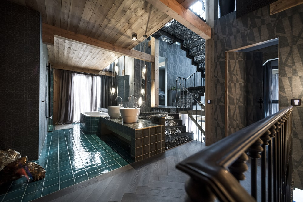 On the side of the intricate staircase is the large bathroom with green tiles and large freestanding sinks.