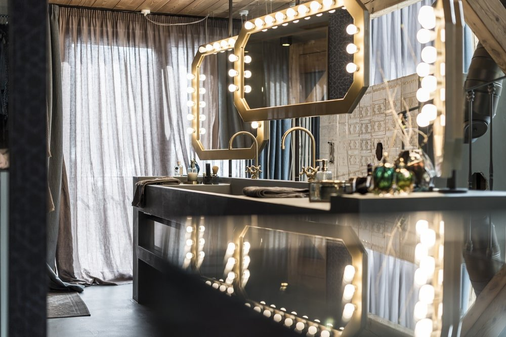 This is a close look at the vanity that is topped iwth a couple of hanging mirrors with warm lights.