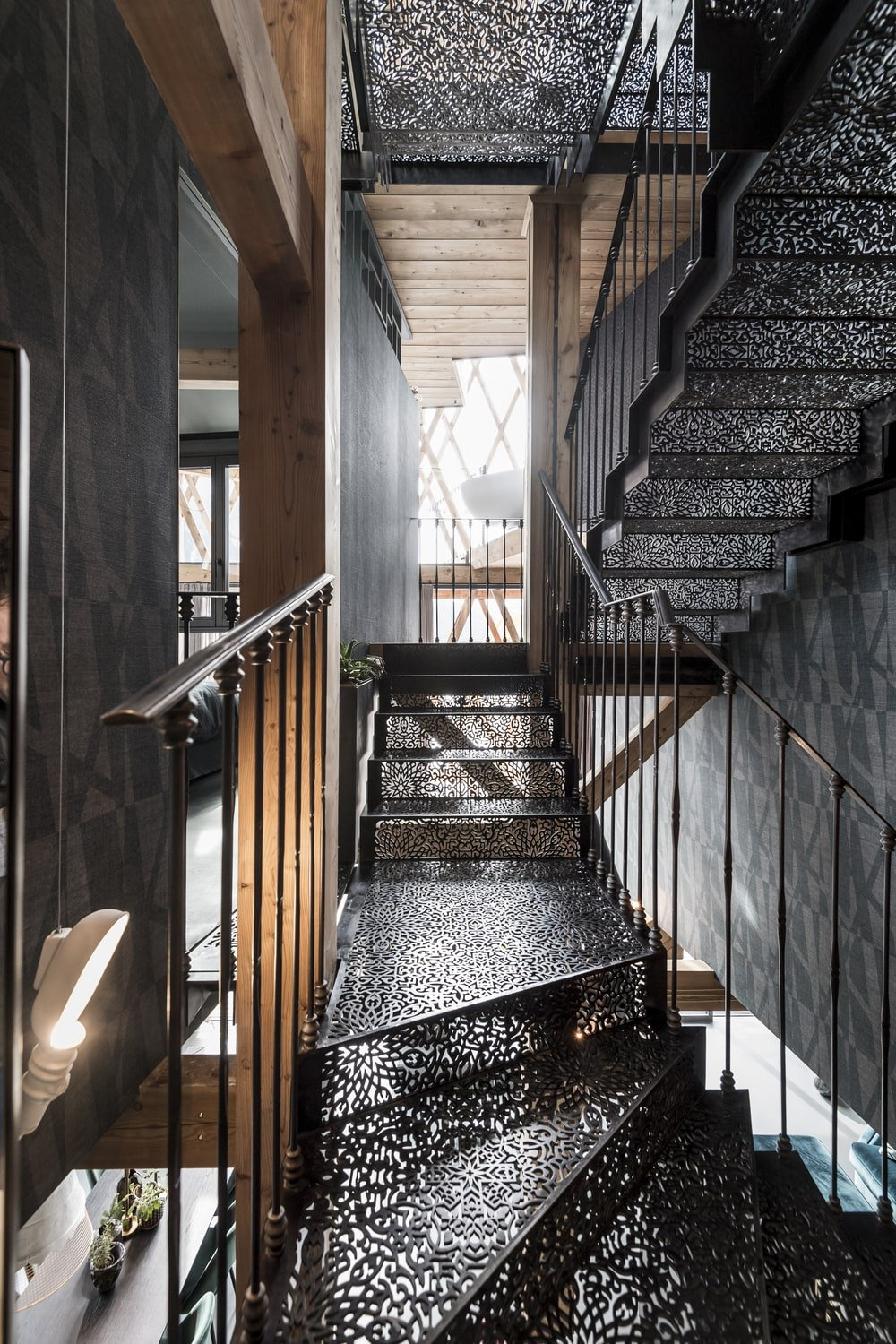 This is a close look at the staircase that has an intricate design and black railings.