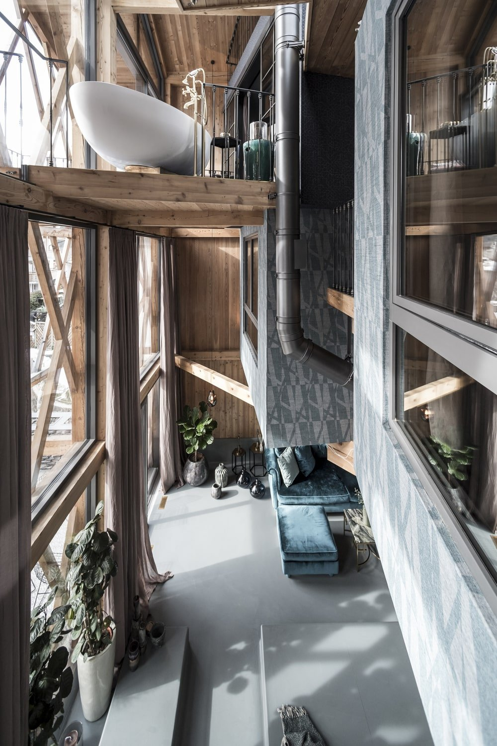 This is a look down on the living room area from the vantage of the indoor balcony showcasing the massive glass wall and wooden accents.
