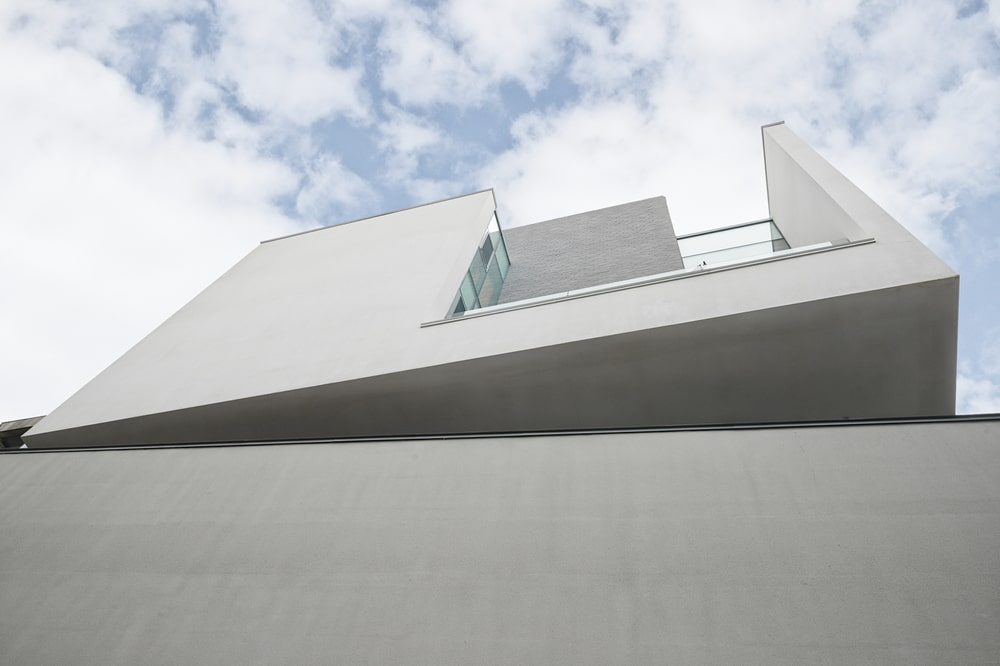 This is a look up at the askew design of the upper floor with bright concrete walls.