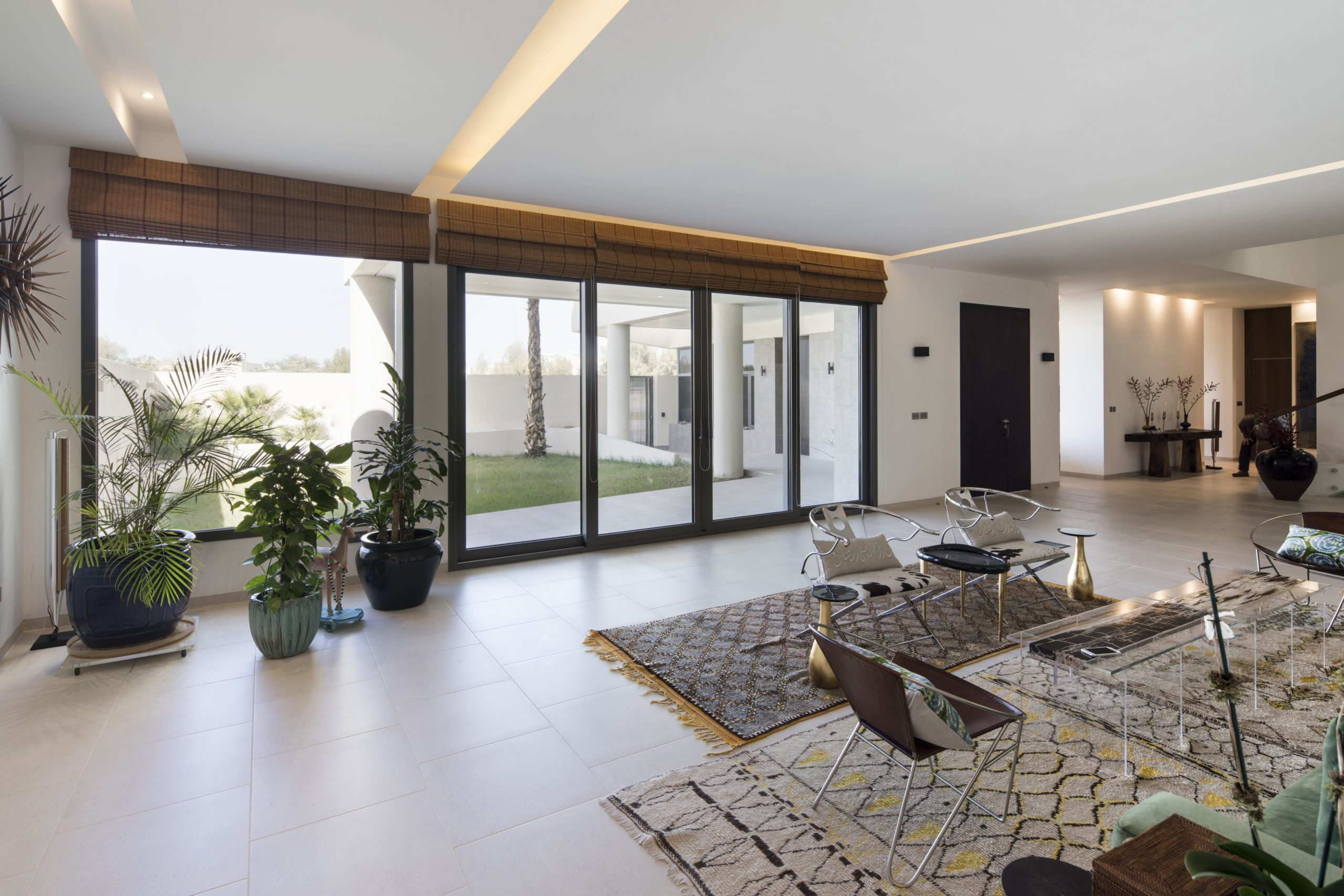 The interiors of the house are brightened by the glass doors that lead to the patio adorned with various potted plants.