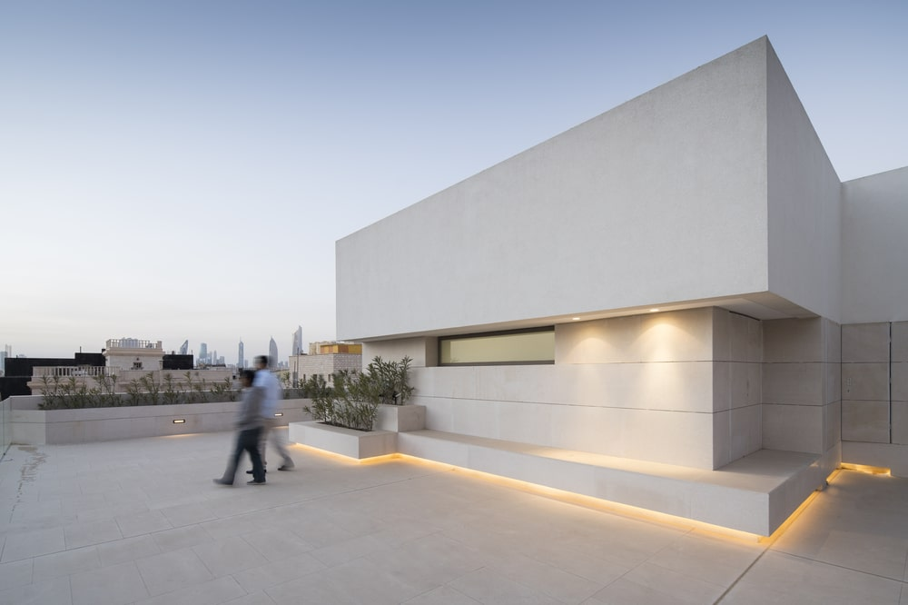 This is the rooftop terrace with modern lighting and concrete planters.
