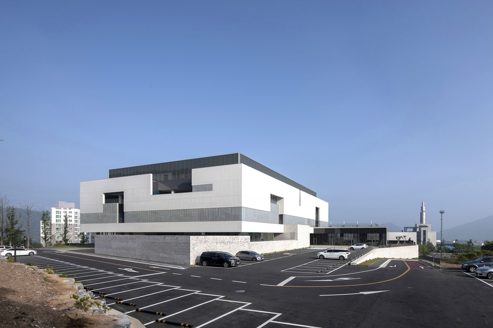 The light exterior wall tone of the building is contrasted by the surrounding asphalt driveway and parking.