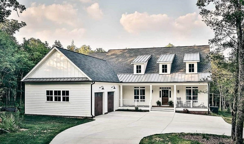This is a look at the front of the farmhouse-style home with dormer windows on its dark roof and a large courtyard in front.