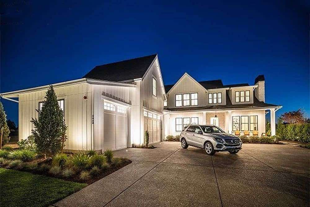 This is a nighttime view of the the farmhouse-style home with white exterior walls complemented by the warm glow of the interior and exterior lights.