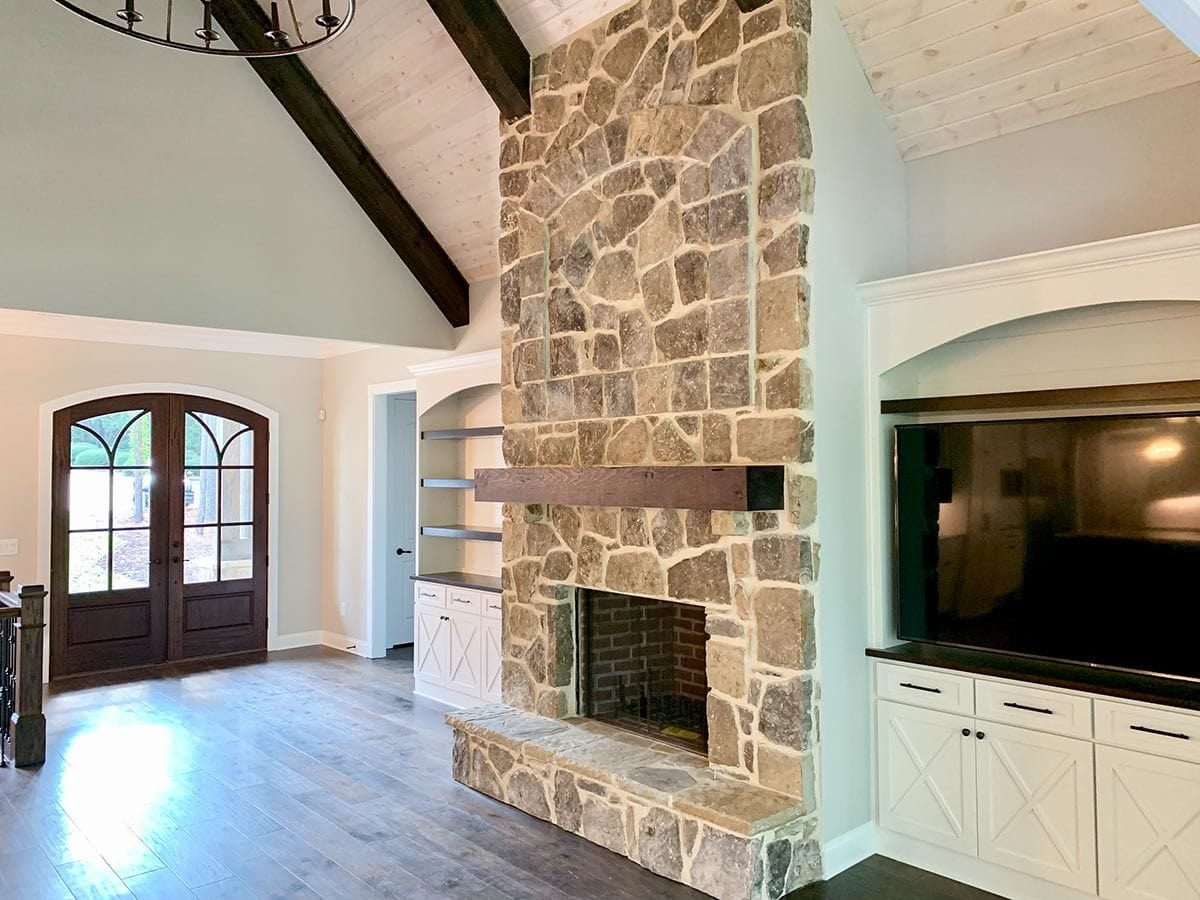 Upon entry, you'll immediately see the living room with a stone fireplace flanked by white built-ins.