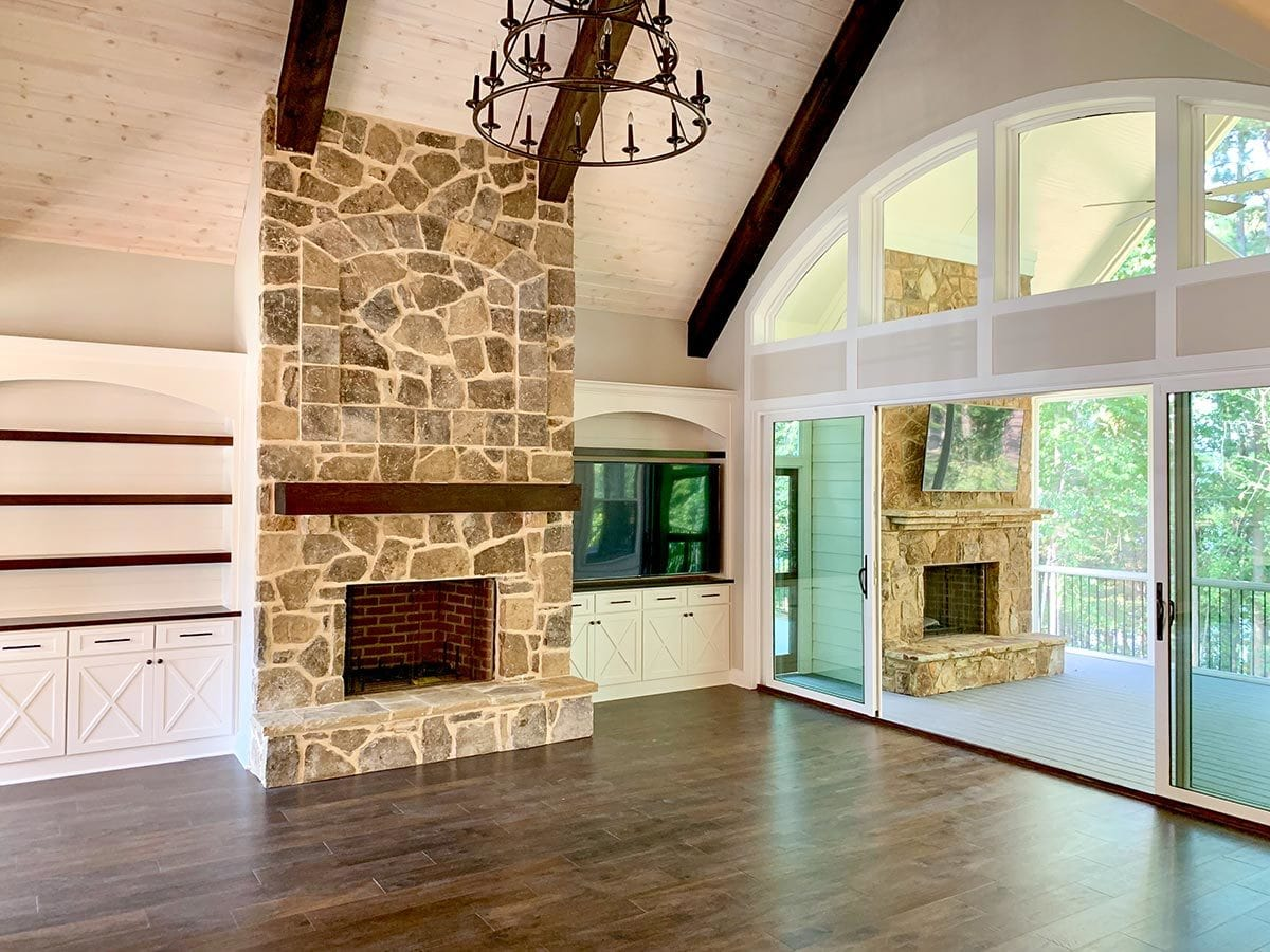 The stone fireplace in the living room is echoed onto the screened porch.