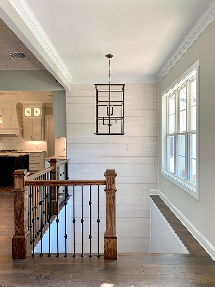 Staircase with wrought iron railings and chandelier leading down the basement.