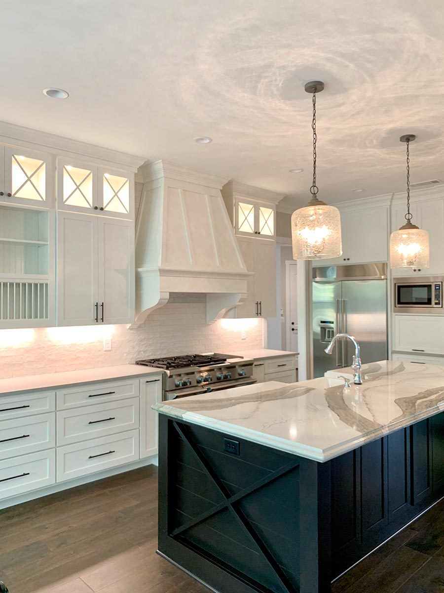 A black kitchen island sets a stunning contrast to the white cabinetry and brick backsplash.