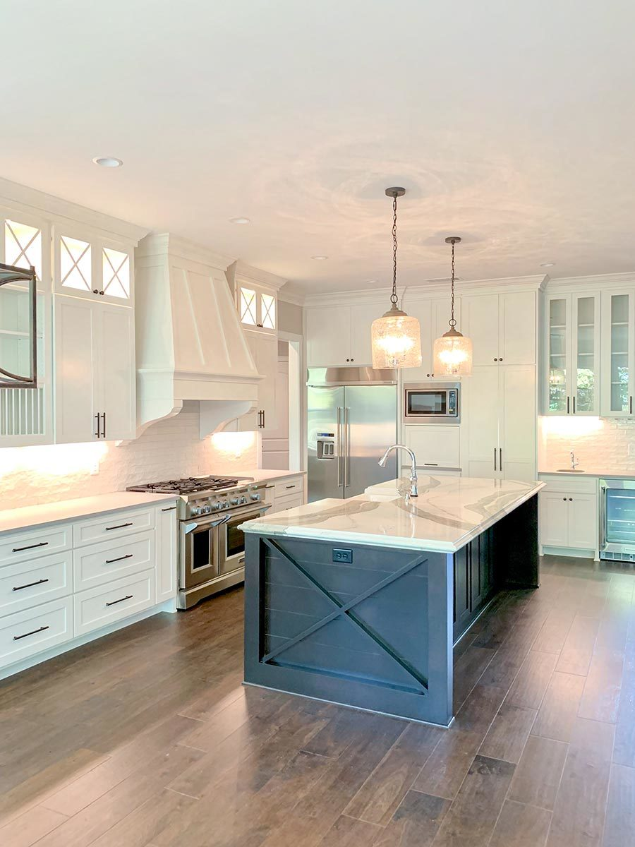 The kitchen includes stainless steel appliances and white marble countertops.