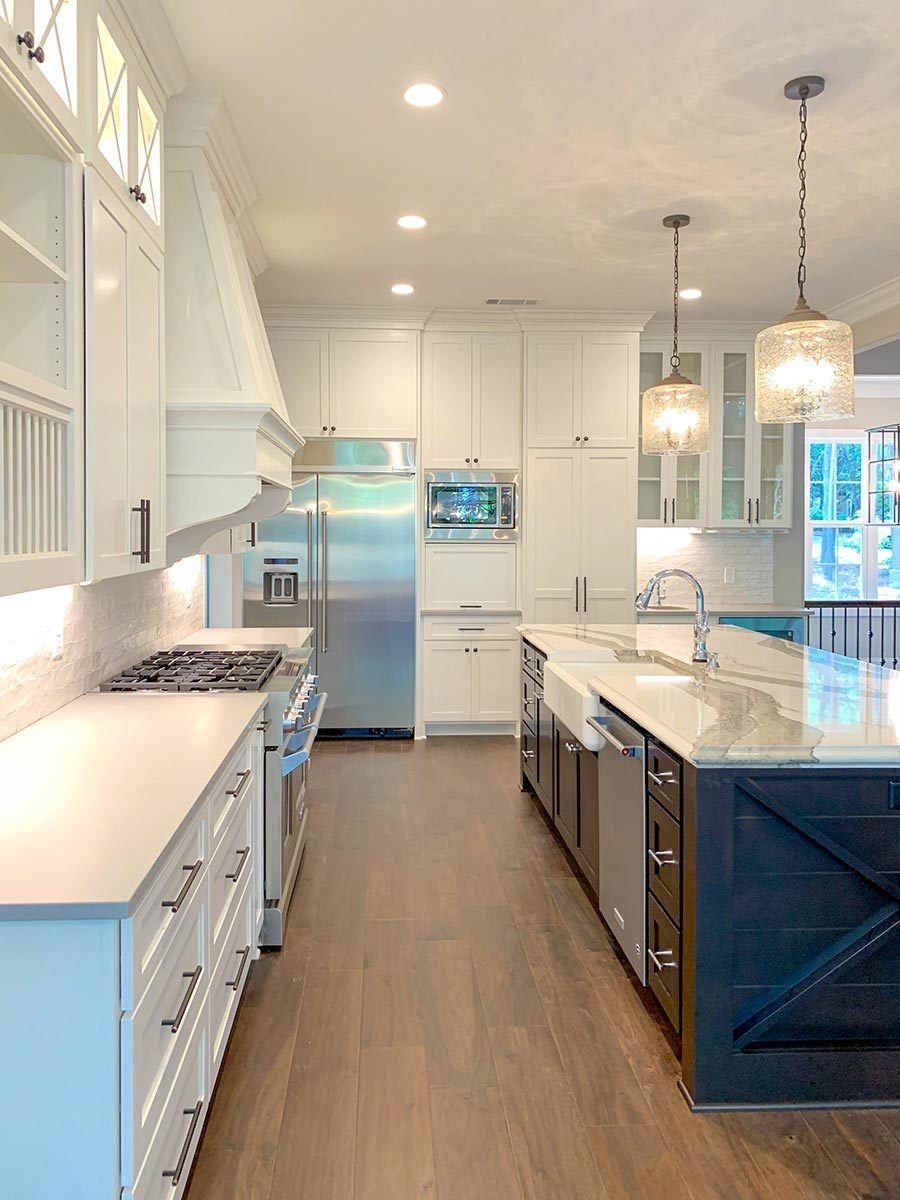 The kitchen island is fitted with a dishwasher and a farmhouse sink paired with a gooseneck faucet.
