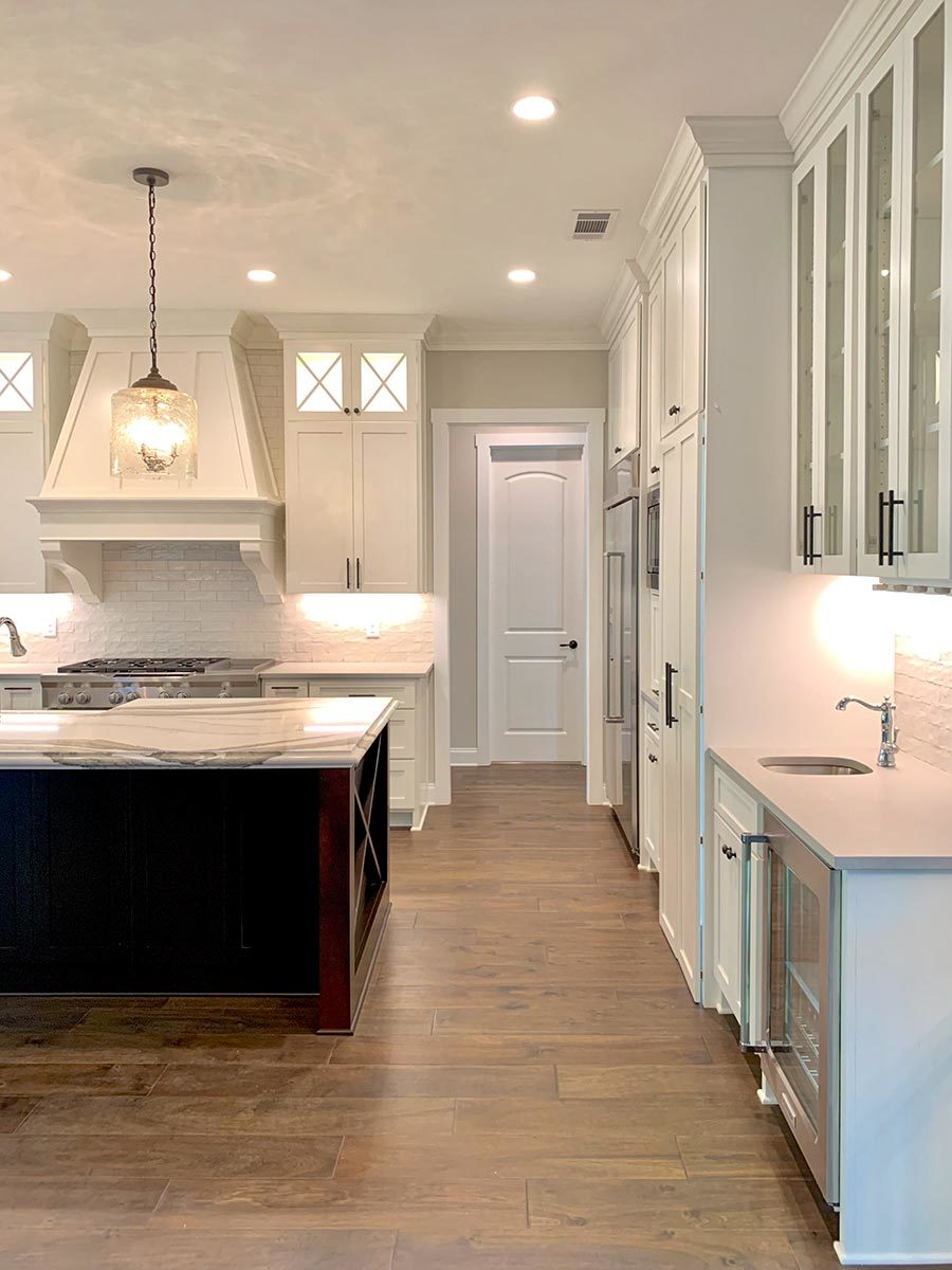 White plank flooring softens the pristine white scheme in the kitchen.