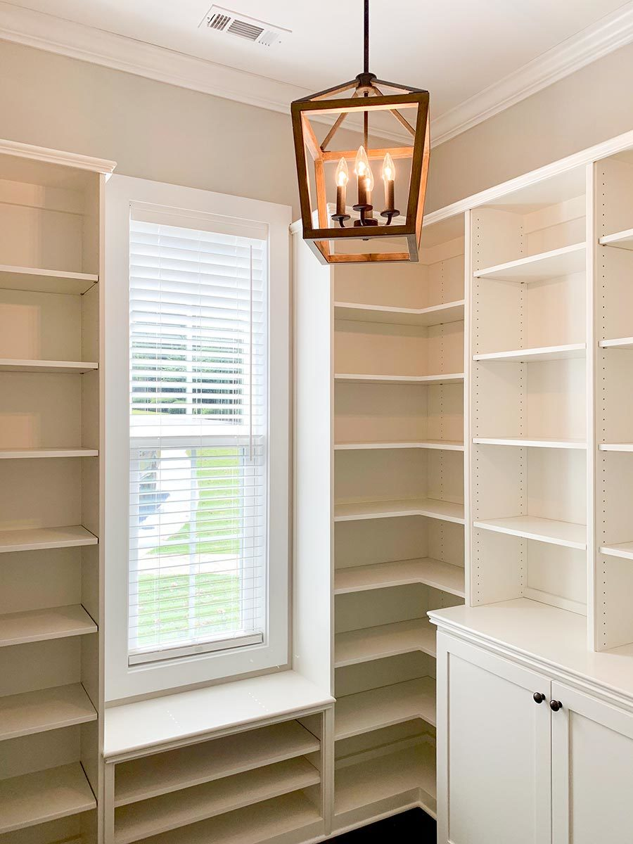 Walk-in pantry filled with built-in shelves and a slim window.